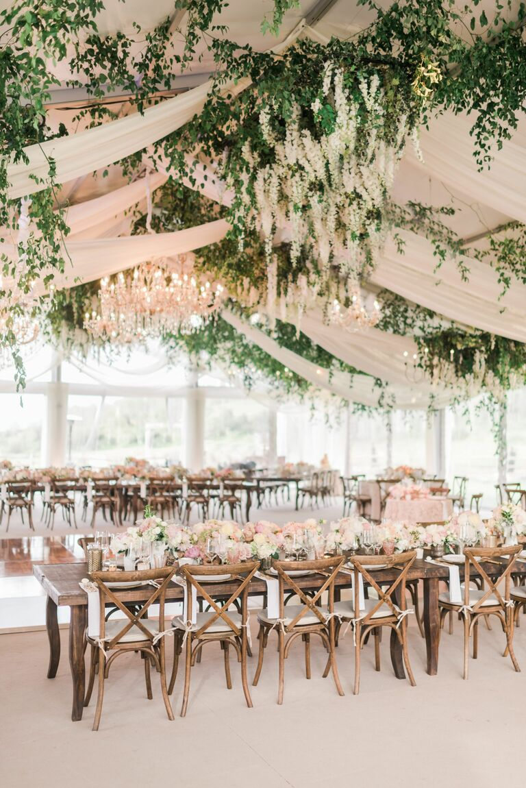 Romantic reception with greenery and chandeliers decorating the ceiling