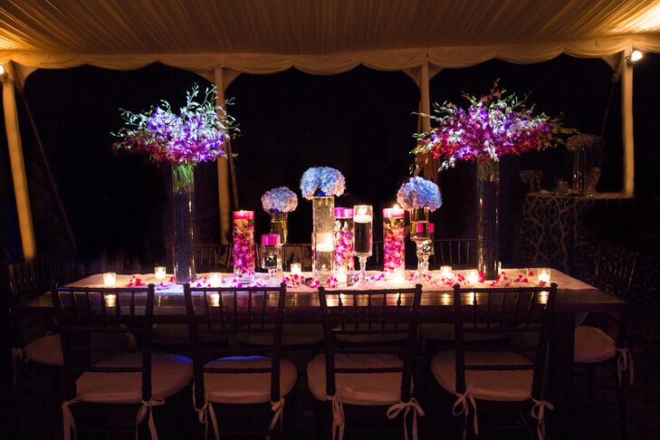 """Picking flowers was the hardest part of wedding planning for Liz because she didn't know much about them. """"I knew I wanted my colors to stand out and I loved the look of submerged flowers—from there, I left it up to the florist."""" says Liz. """"She even incorporated fresh raspberries and blue berries into the bases of the tall vases!"""" rnrn"""