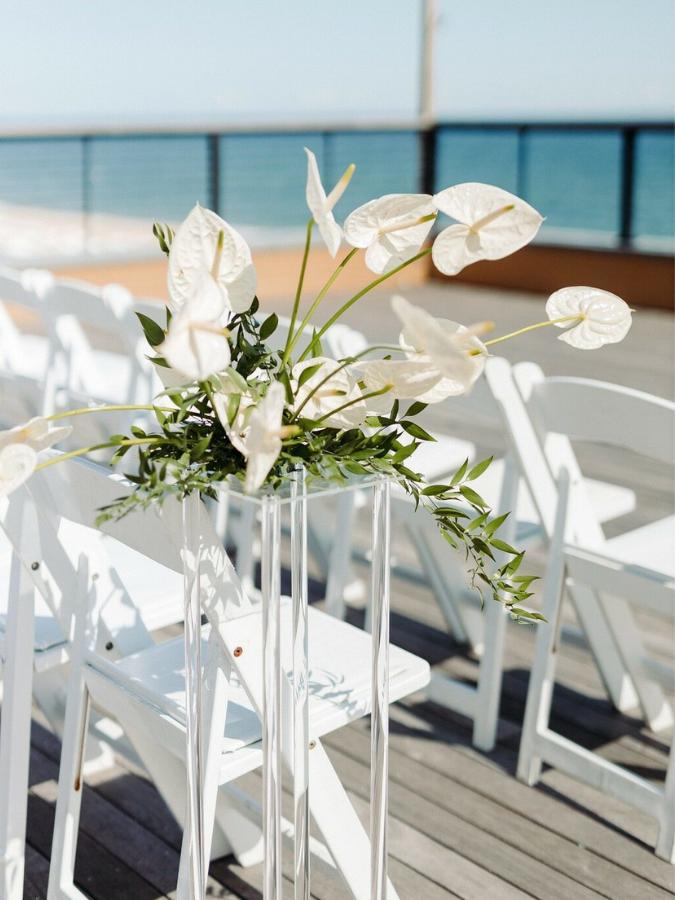 anthurium floral arrangement on pedestal at oceanside wedding ceremony