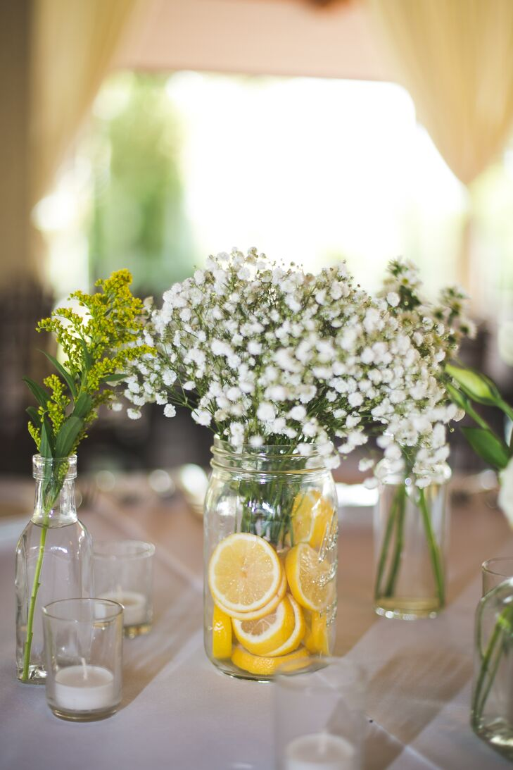 Table centerpieces included both mason jars filled with sliced lemons and baby's breath and farm fresh rustic silver containers.