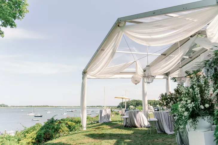 Open-air tent with chandeliers at waterfront reception
