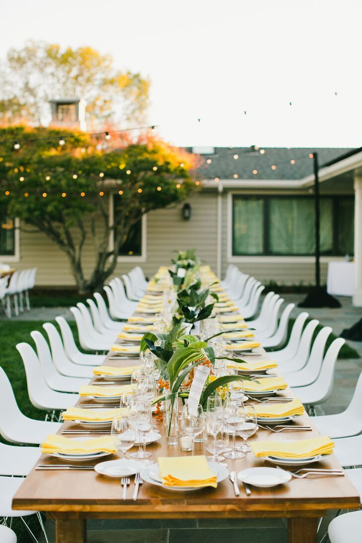 At the reception, long wooden banquet tables were topped with clear vases of fresh fernlike greens. Yellow napkins added a pop of color. String lighting hung overhead.