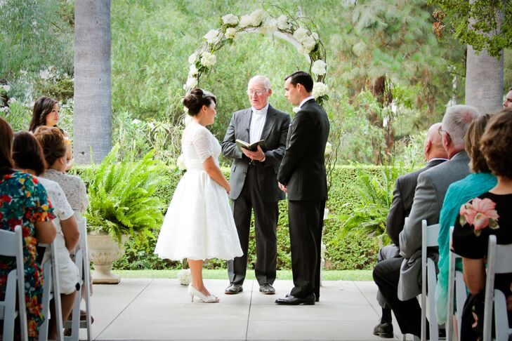 Brandy and John stood on the patio at the Lindley-Scott House as their officiant conducted their ceremony. Brandy wore an ivory dress adorned with a skirt in a ball-gown style on the wedding day, while John wore a vintage-inspired black tuxedo.