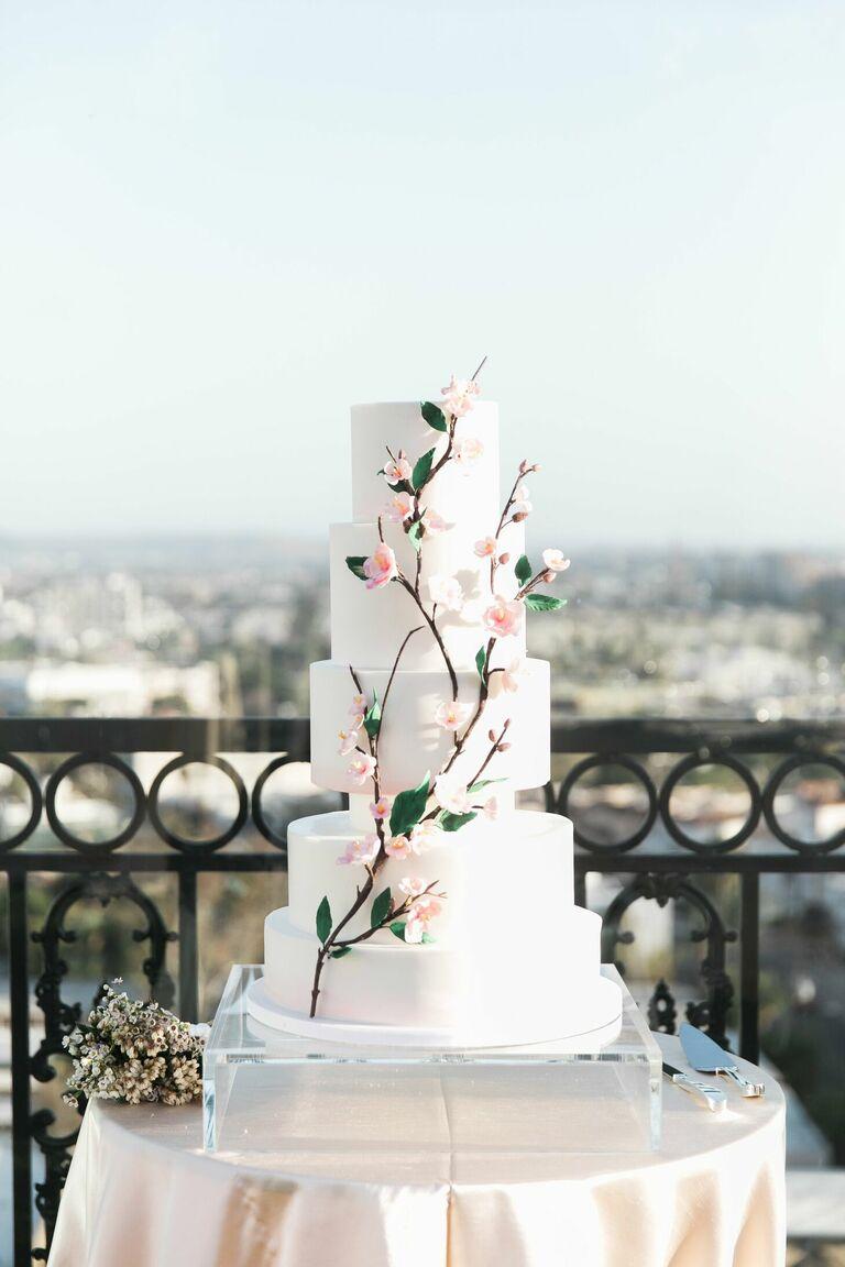 Modern white wedding cake with cherry blossom decorations