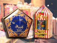 Chocolate Frogs in elegant pentagon purple container with gilded gold details and Every Flavor Beans in circus-themed packaging