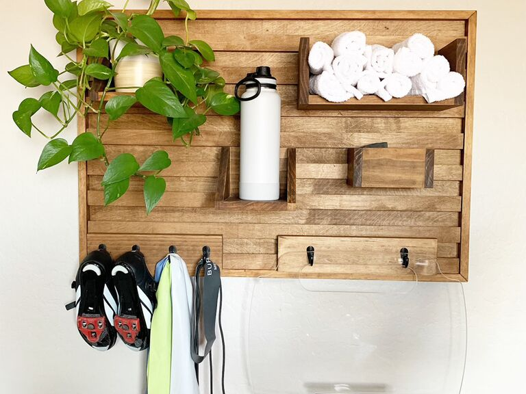 Wooden wall organizer with shelves and black hooks