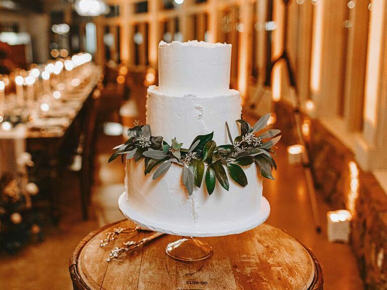 Simple rustic wedding cake with white icing and garland of eucalyptus leaves