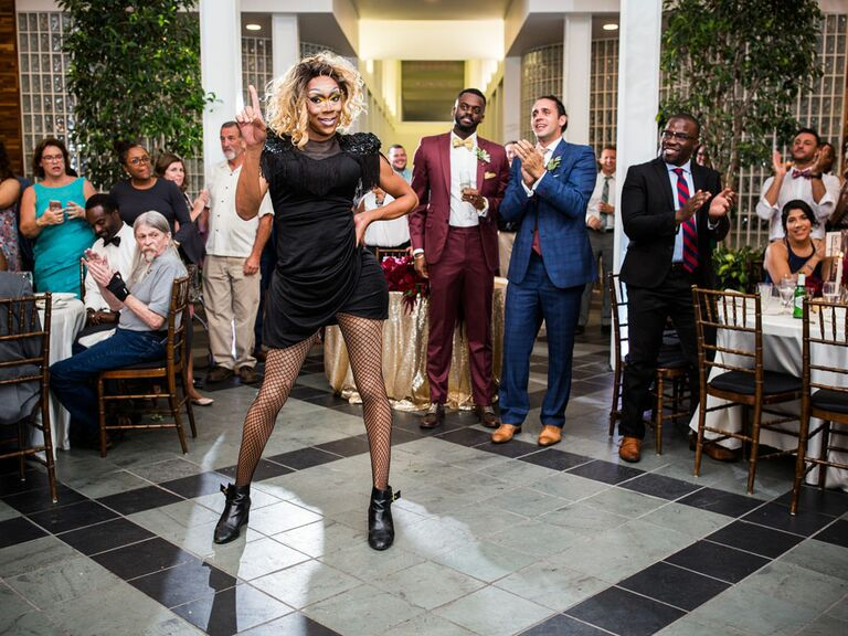 Grooms with guests watching drag performance at wedding reception