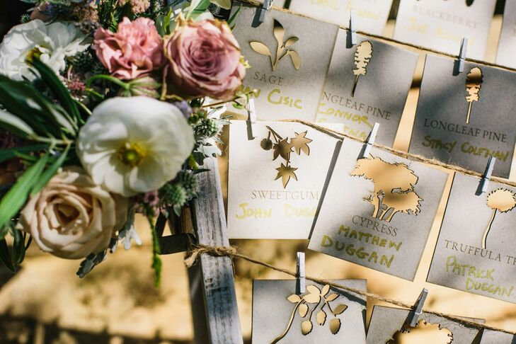 """Instead of traditional table numbers, laser-cut escort cards included every table name. """"Those were my favorite design detail,"""" Claire says. """"We asked Madeline Trait to design the cards with cutouts of our favorite trees and flowers."""""""