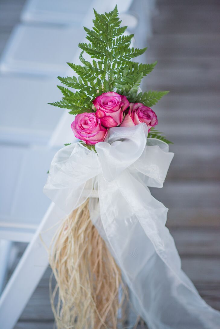 The couple decorated their ceremony aisle with pink roses, white ribbon bows, straw and starfish to complement their beach theme.