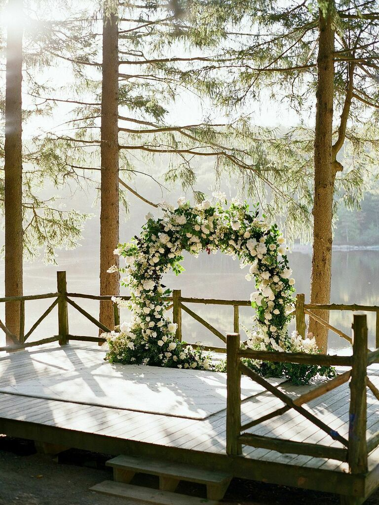 Lush white floral ceremony arch at outdoor lakeside wedding