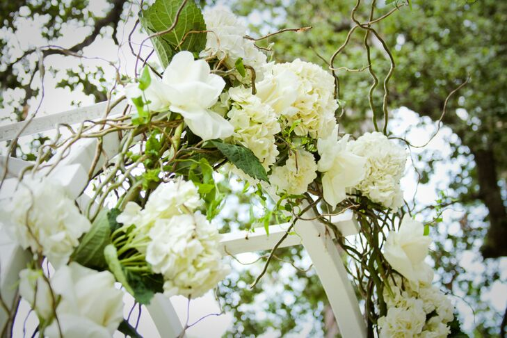 Brandy and John were married at the white wooden wedding arch, adorned with ivory  hydrangeas and roses mixed with green leaves and branches.