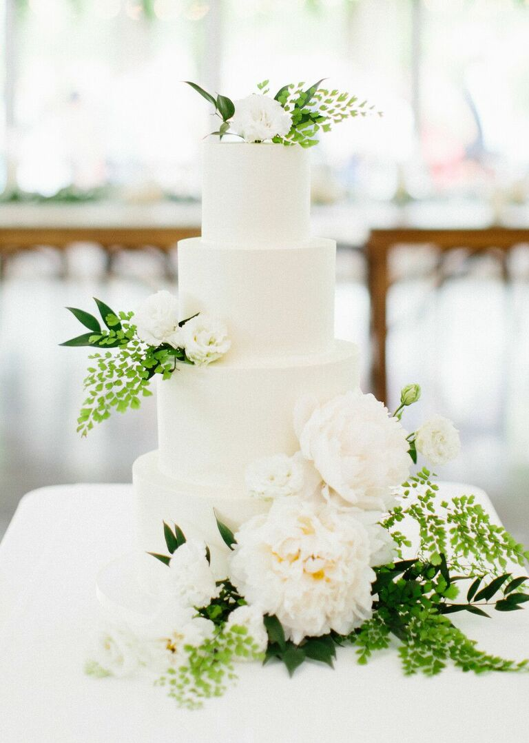 All-white four-tier cake with white flowers and greenery decorations.