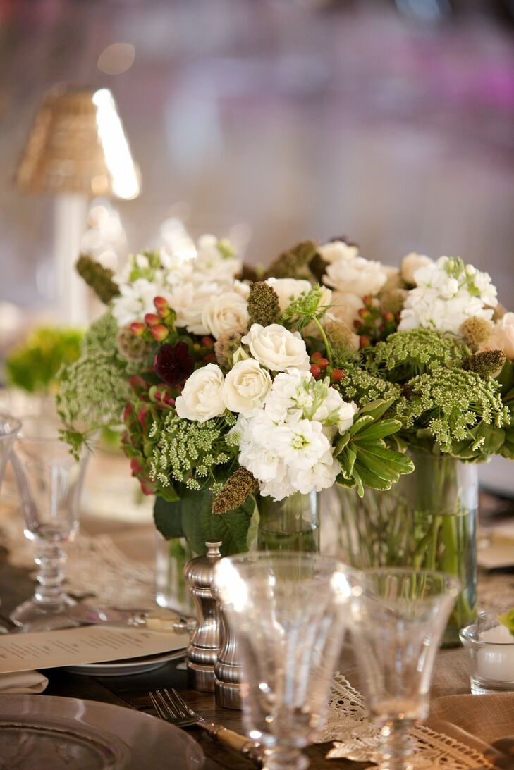 The wooden farm tables were topped with lace-trimmed runners and organic arrangements of pittosporum, Queen Anne's lace, spray roses, hypericum berries, burgundy scabiosa, scabiosa pods, brown cosmos and millet grass.