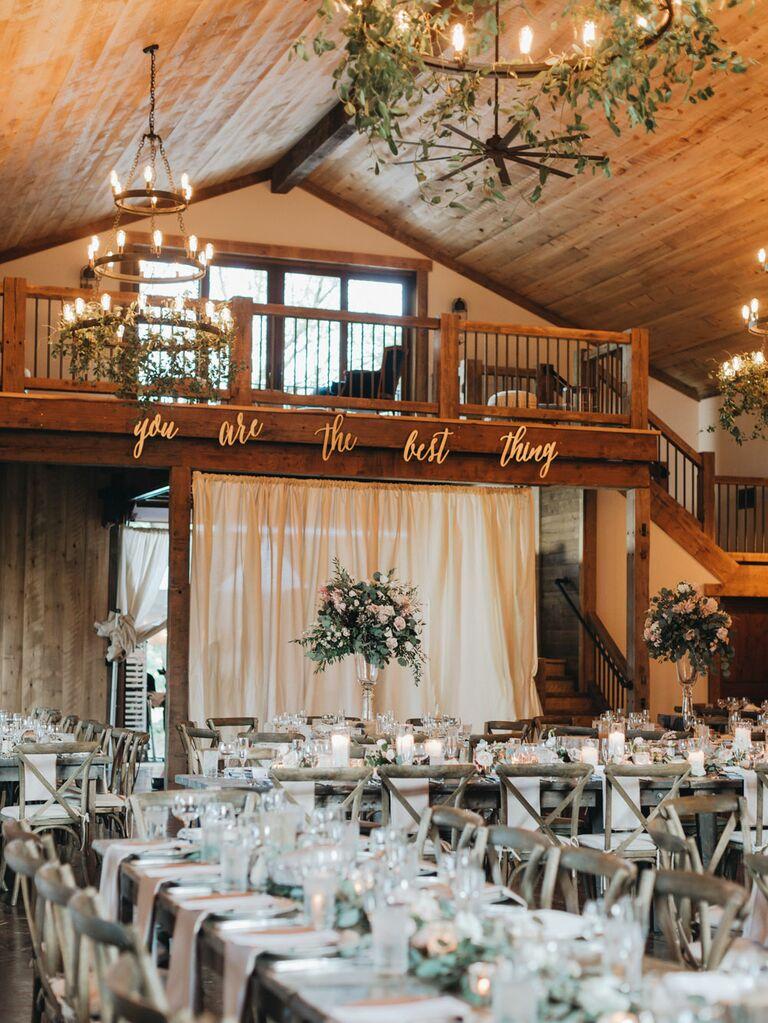 Rustic barn wedding reception with sign lyric decorations on wall