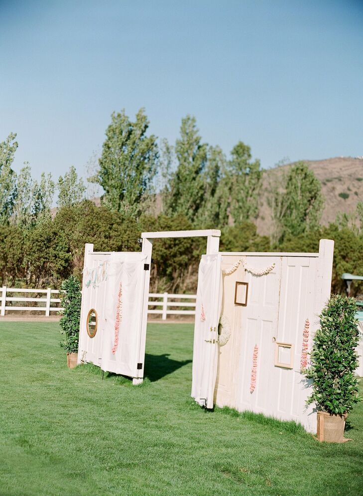 The wedding party entered into the ceremony through a wall of upcycled doors that Gregger and his father built. The couple's florist then decorated the wall with floral wreaths and carnation garlands.