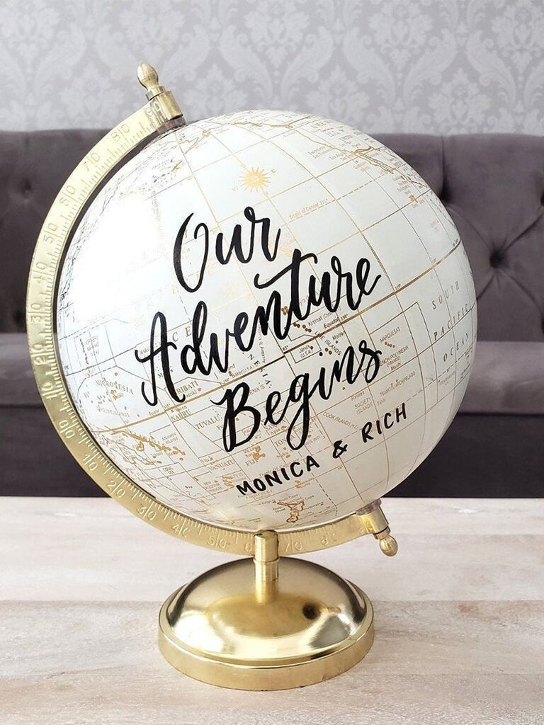 'Our Adventure Begins' and couple's names in black script on white globe with gold stand