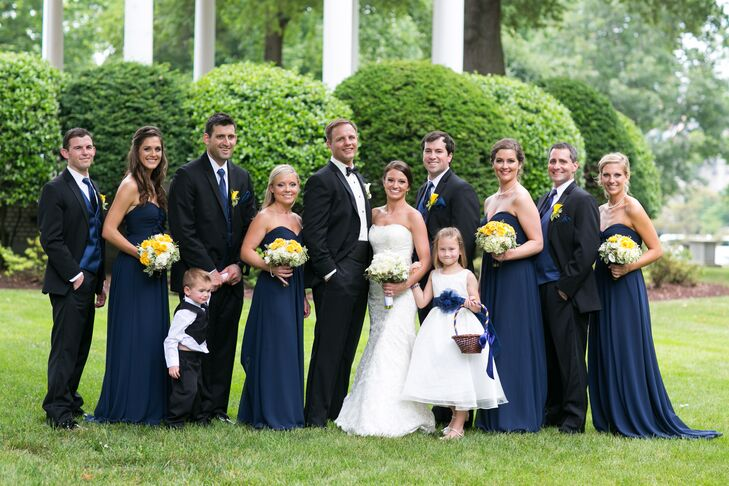 Under the US Naval Academy's navy and gold hues, Kara's bridesmaids wore these chic, floor-length navy dresses by Bill Levkoff. Each had a strapless sweetheart neckline that was only enhanced with their classic pearl necklaces. Each bouquet brought out the gold-inspired hue with yellow roses.
