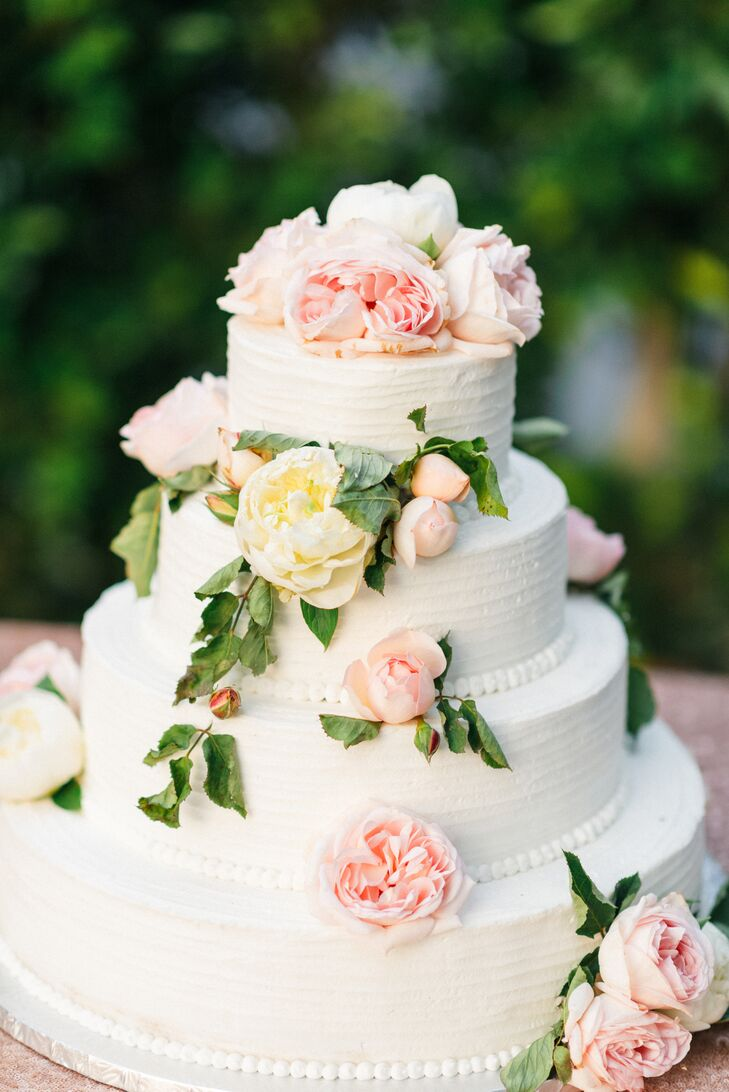"""""""Our cake was simple—three tiers with white whipped frosting, fresh cascading roses, peonies and greenery,"""" Andrea says. """"It was chocolate with fresh whipped cream and strawberries inside—and it was consumed entirely that night."""""""