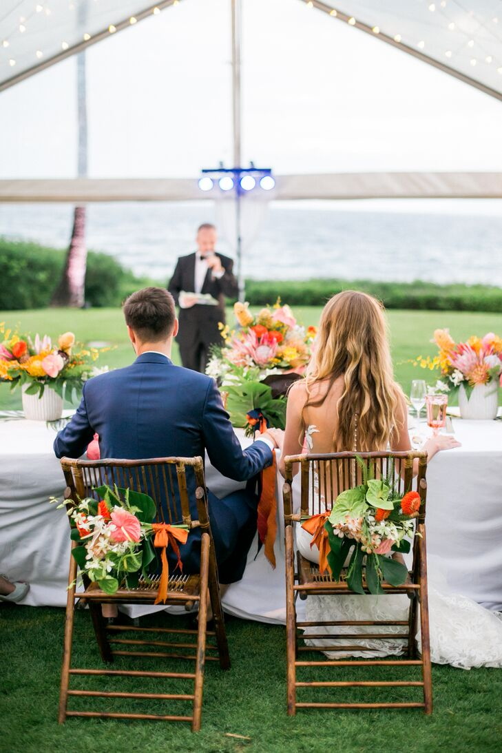 Florist Lauryl Lane crafted colorful tropical flower chair decorations for the bride and groom.