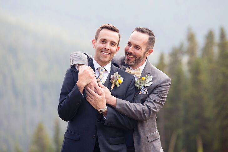 """We wanted a rustic mountain theme that still had a bit of modern elegance,"""" David says. With the spectacular landscape providing endless rustic appeal, the couple brought in elements of refined flair through their attire. Jeremy donned a classic navy three-piece suit, while David sported a windowpane gray three-piece suit. To coordinate their looks in a subtle way, Jeremy wore a gray vest and a yellow plaid tie, while David opted for a navy vest and yellow checked bow tie."""