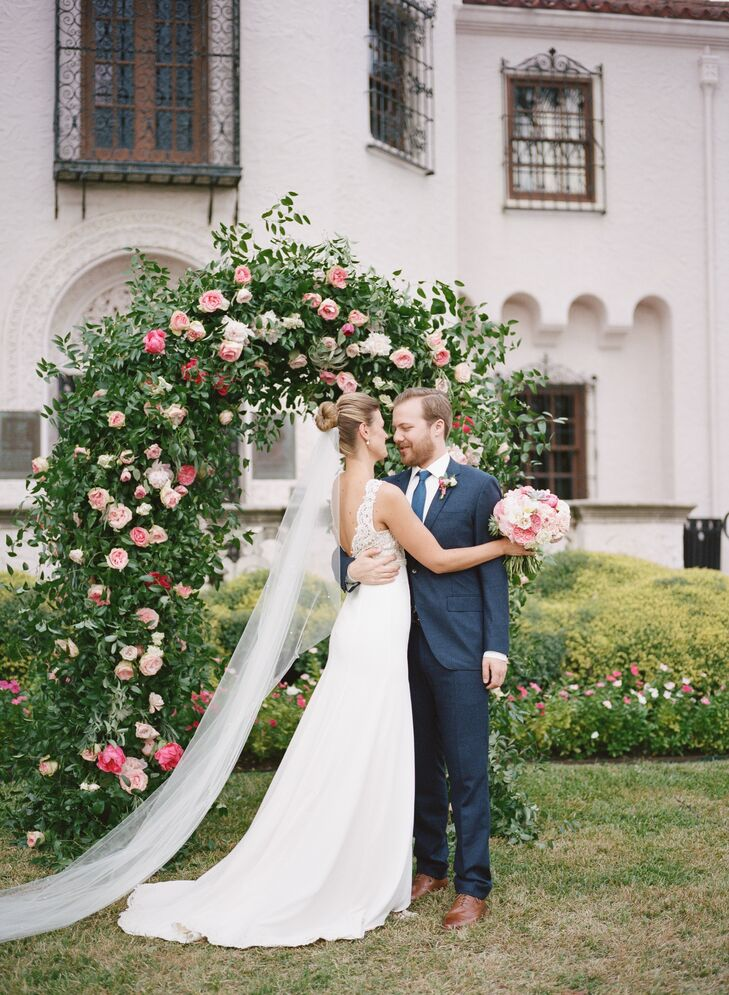 """Alicia and Ian said """"I do"""" under an arch covered in greenery and pink garden roses."""