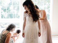 Bride getting ready with assistance from her maid of honor
