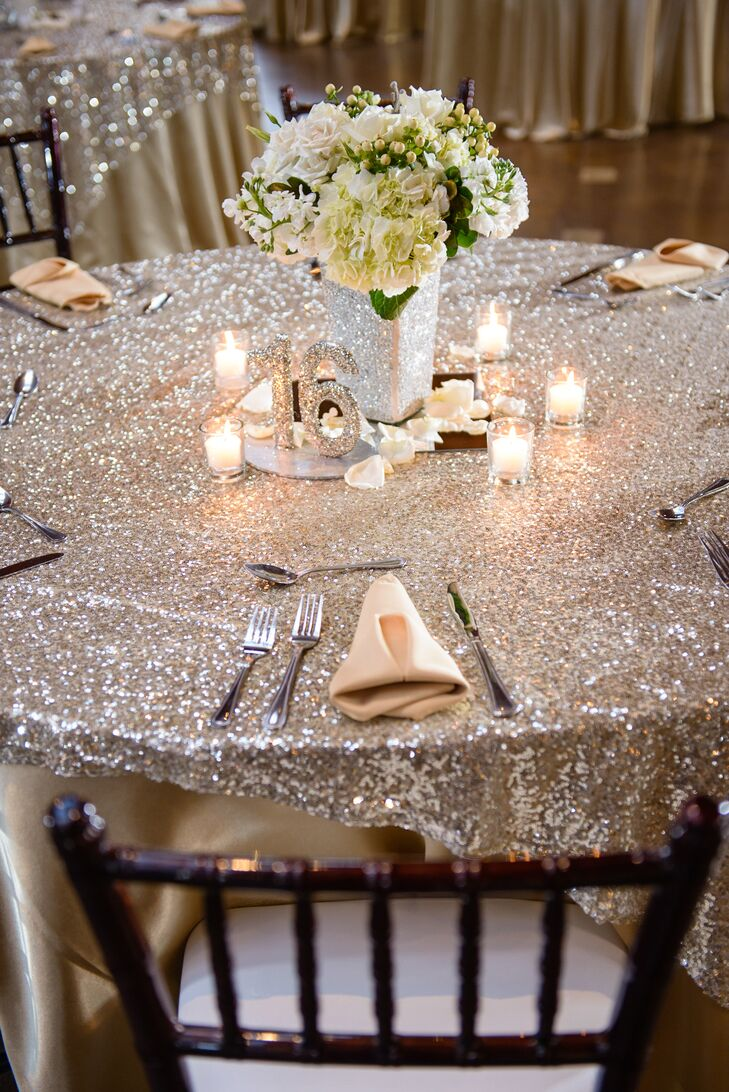 """The couple designed their silver glitzy silver decor around their New Year's Eve inspiration. Glitter accents popped against a black, white gold color palette and simple white flower arrangements filled sparkling vases. """"To pull the flowers in, we had some greenery in the arrangements brushed with gold paint,"""" says Rachel."""