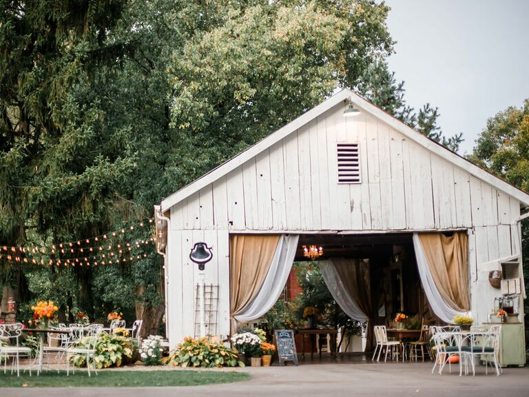 Barn wedding venue with draped fabric over entrance and string lights