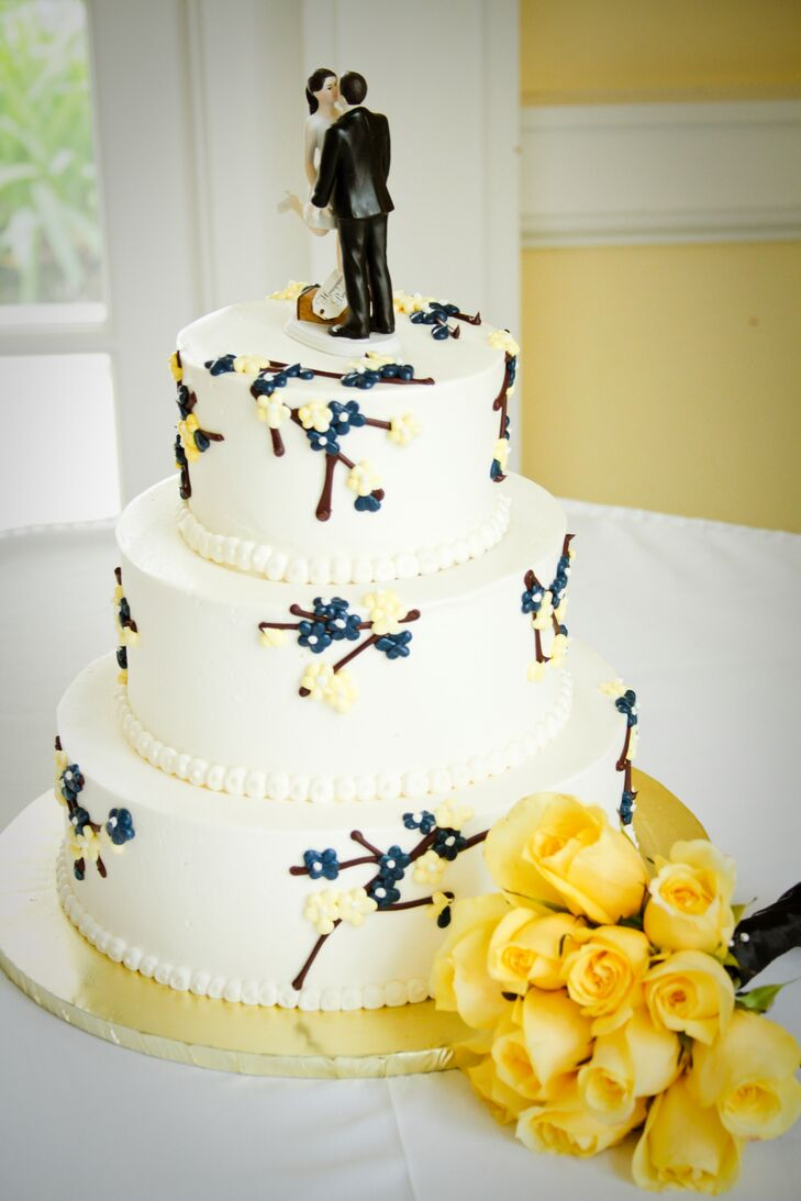 """The white wedding cake was decorated with sugar designs depicting flowers on tree branches, topped with classic bride and groom figurines. """"We absolutely loved the three-tier cake, which included red velvet, white cake and lemon cake, with layers of buttercream and cream cheese throughout."""""""
