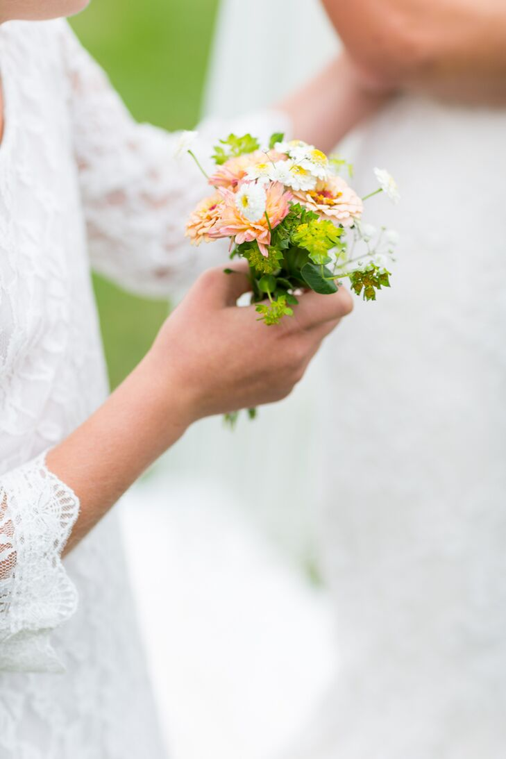To add a splash of playful color to the flower girls' white lace dresses, Molly's mother created small bundles of mums, daisies and zinias in cheerful shades of peach and pink for the girls to carry down the aisle.