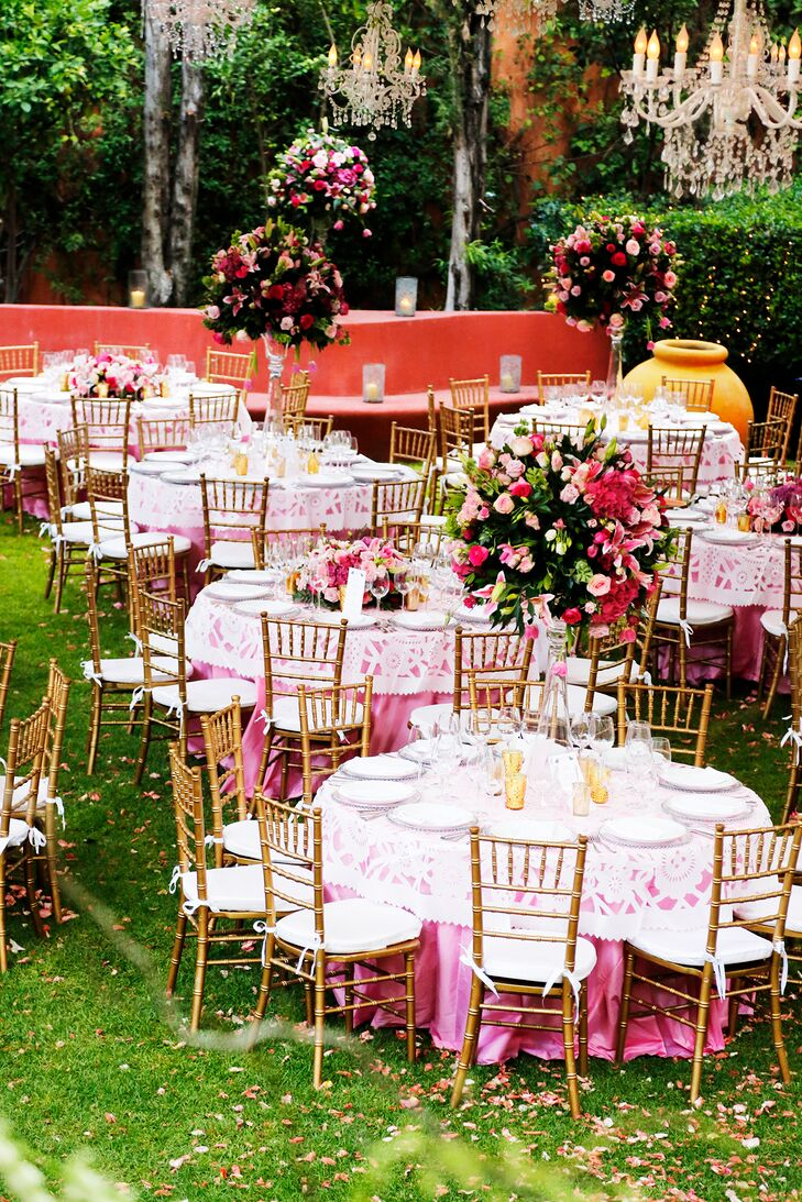 While the wedding party was out in the mojiganga parade, wedding planners at Penzi transformed the backyard at Casa Hyder into a beautiful pink reception full of tall, bursting arrangements of pink flowers and pink petals between all the pink dining tables.