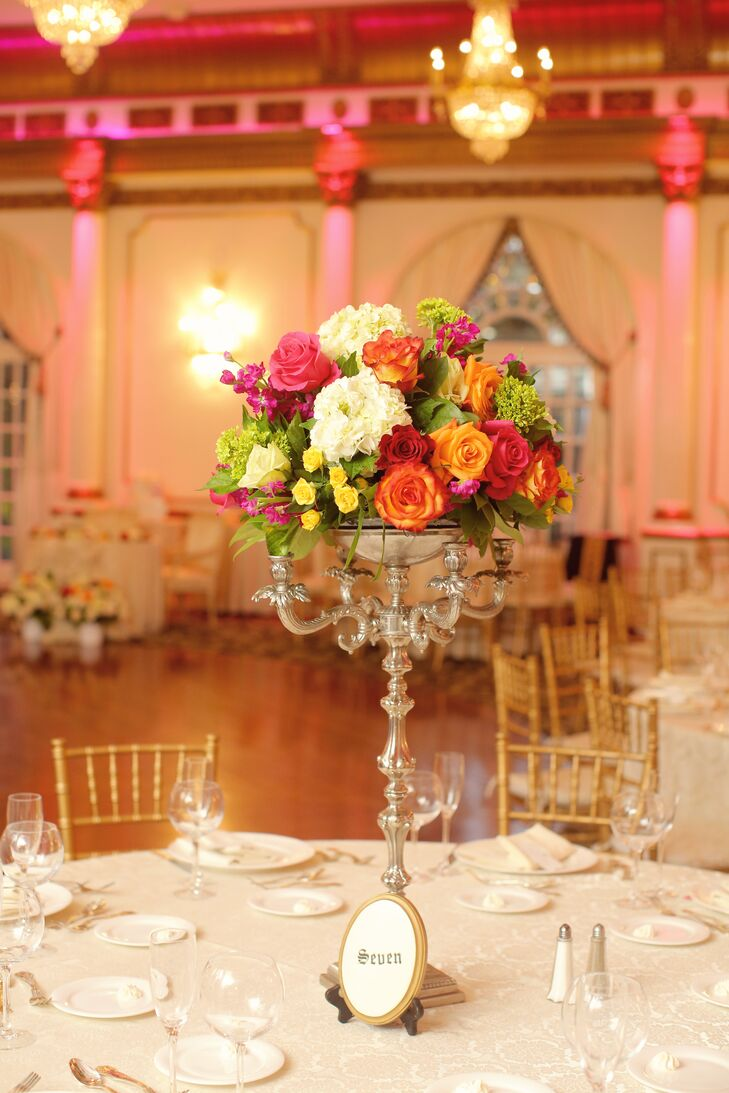"""""""We picked red wine as our primary color, but couldn't choose a second or third color - so we thought, Why not use them all?"""" Michelle says. Their centerpiece did just that and brought out every hue! Each family-style table was accented with this tall silver candelabra topped with flowers. Orange, red, pink and ivory roses as well as purple delphiniums, yellow spray roses, white hydrangeas and mini green hydrangeas all decorated the elegant stands."""