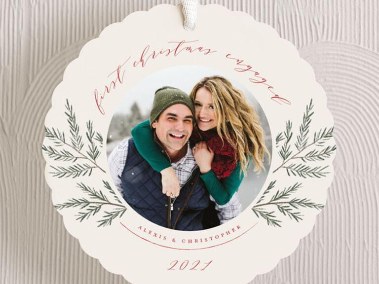 Circle with scalloped edges, personalized photo bordered by greenery and 'first christmas engaged' in elegant red script