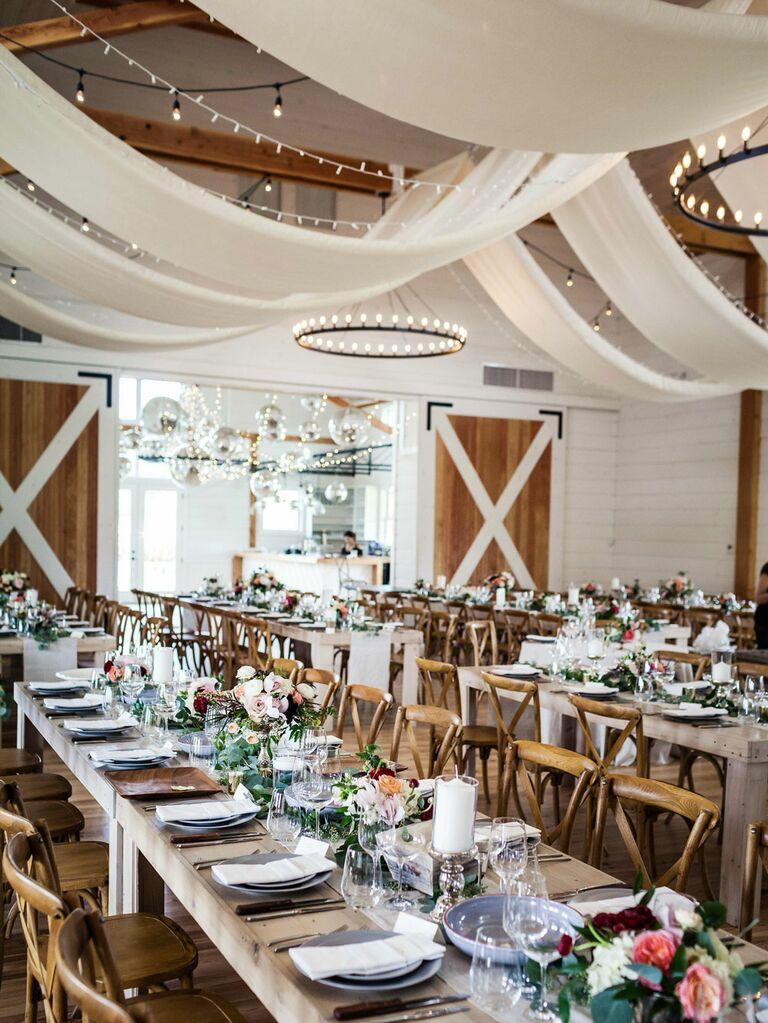 Romantic barn wedding venue with white fabric draped across ceilings
