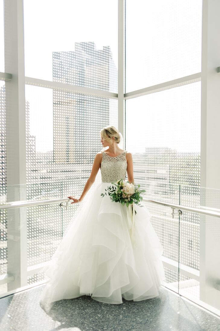 """""""I had decided on my dress months before we even got engaged,"""" Millie says. She fell in love with a Hayley Paige Dori gown with a high neck, a tulle skirt, and a dramatic low back. For her accessories she wore borrowed jewelry from family members for an especially sentimental look."""