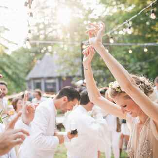 Bride, groom, guests dancing at wedding reception