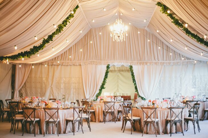 To create an elegant look with a rustic, Italian vibe, the reception tent was draped with airy fabric, lush green garlands and bistro lights. A crystal chandelier added a touch of formality to the space.