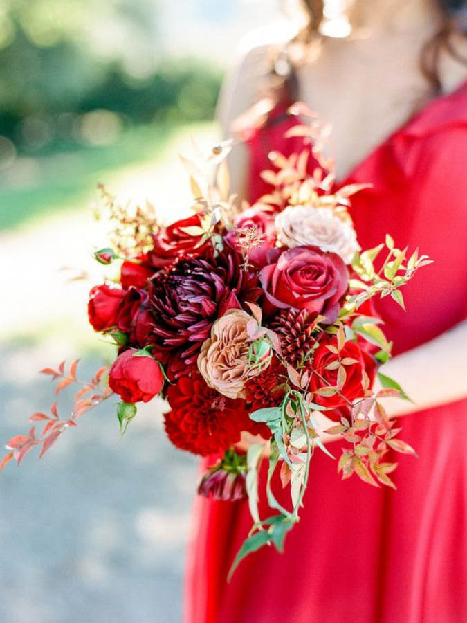 Bridesmaid in red dress holding red bouquet