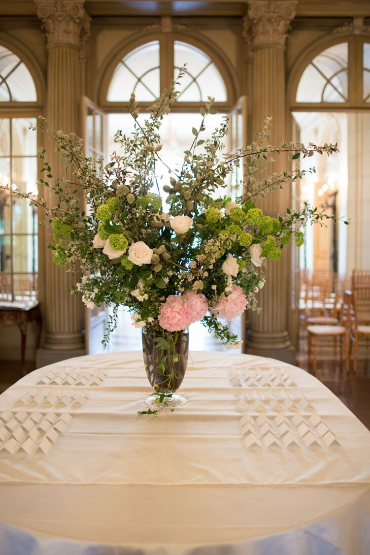 A statement floral arrangement decorated the simple escort card table.