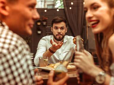 man trying to speak to couple who is engrossed in their own conversation