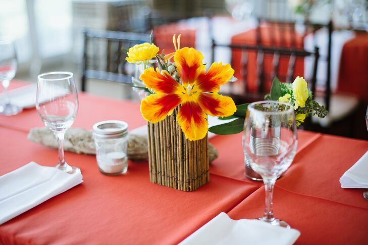 Full, open tulips and ranunculus were paired with silver brunia and dusty miller on guest tables. Tin cans filled with flowers and Mason jar votives surrounded each centerpiece.