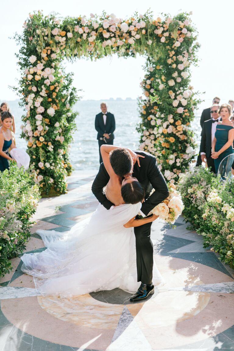 caila quinn wedding floral arch kiss