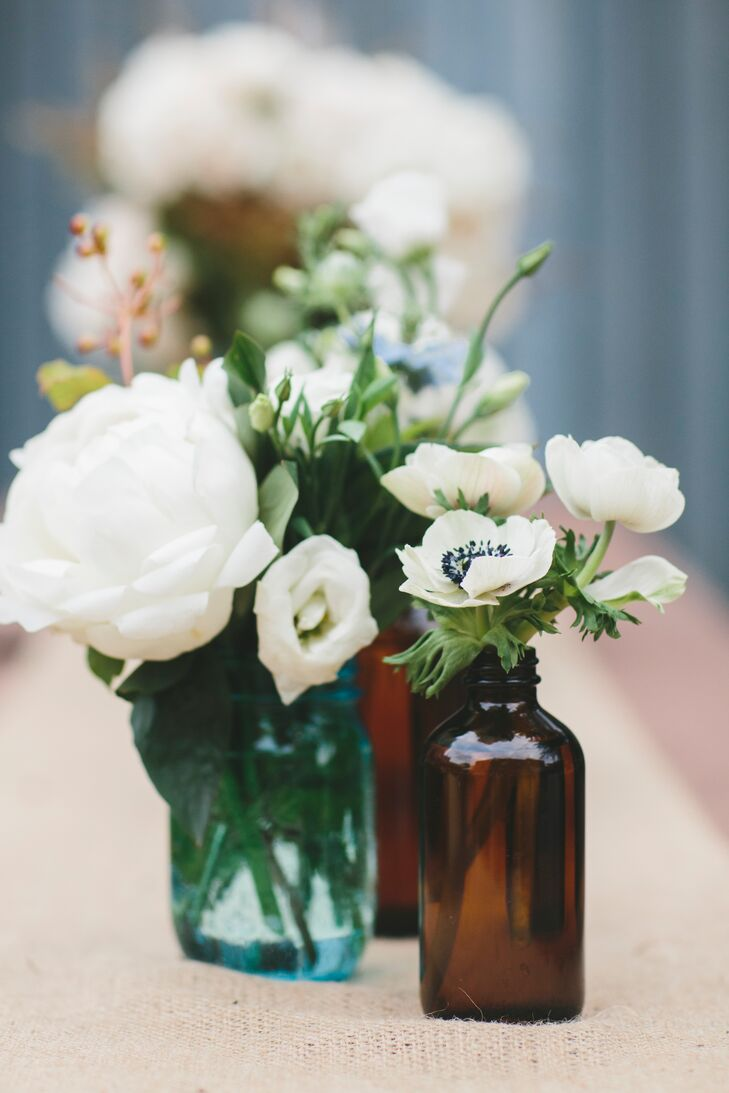 To play up the vintage Americana theme, Jen collected Mason Jars and vintage medicine bottles for the reception centerpieces. The florists at Homecoming in Brooklyn, NY then filled the rustic vessels with arrangements of bright white flowers including anemones, peonies, garden roses and eucalyptus.