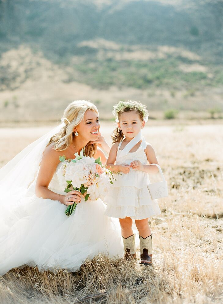 The flower girl wore a layered lace dress with a criss-cross back, cowboy boots and a simple baby's breath flower crown.