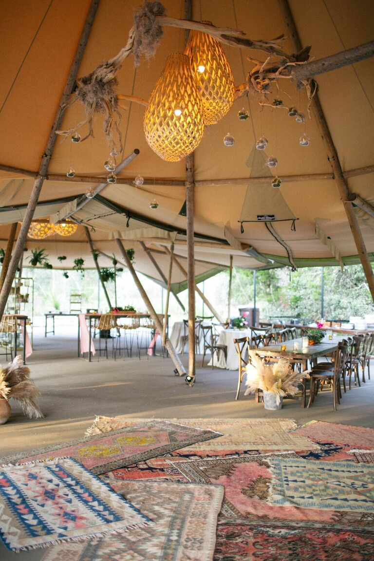 Tented reception with chandeliers and rugs for decoration