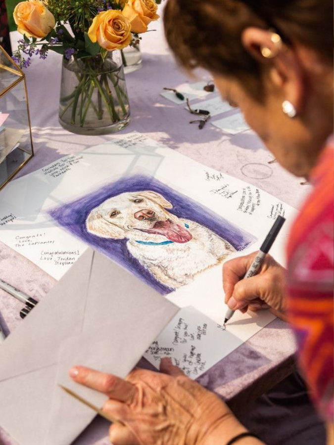 Guest writing on guest book sign with picture of dog
