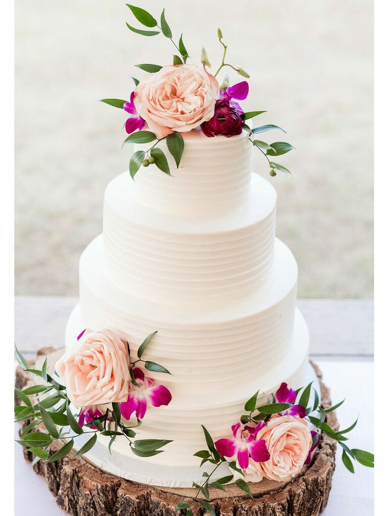Simple rustic wedding cake with white icing and fresh flowers on tree stump cake stand