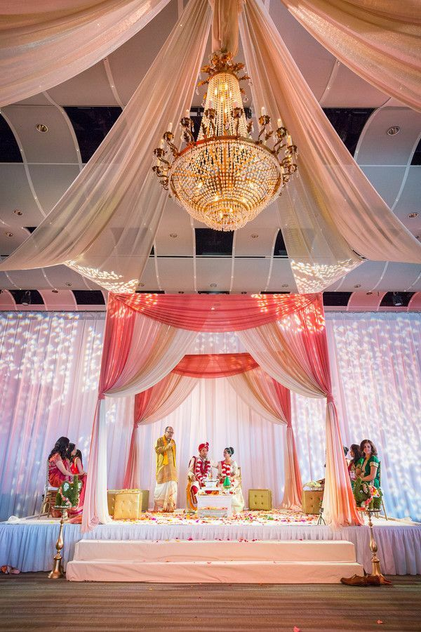 Mandap in hotel ballroom with crystal chandelier and fabric draping