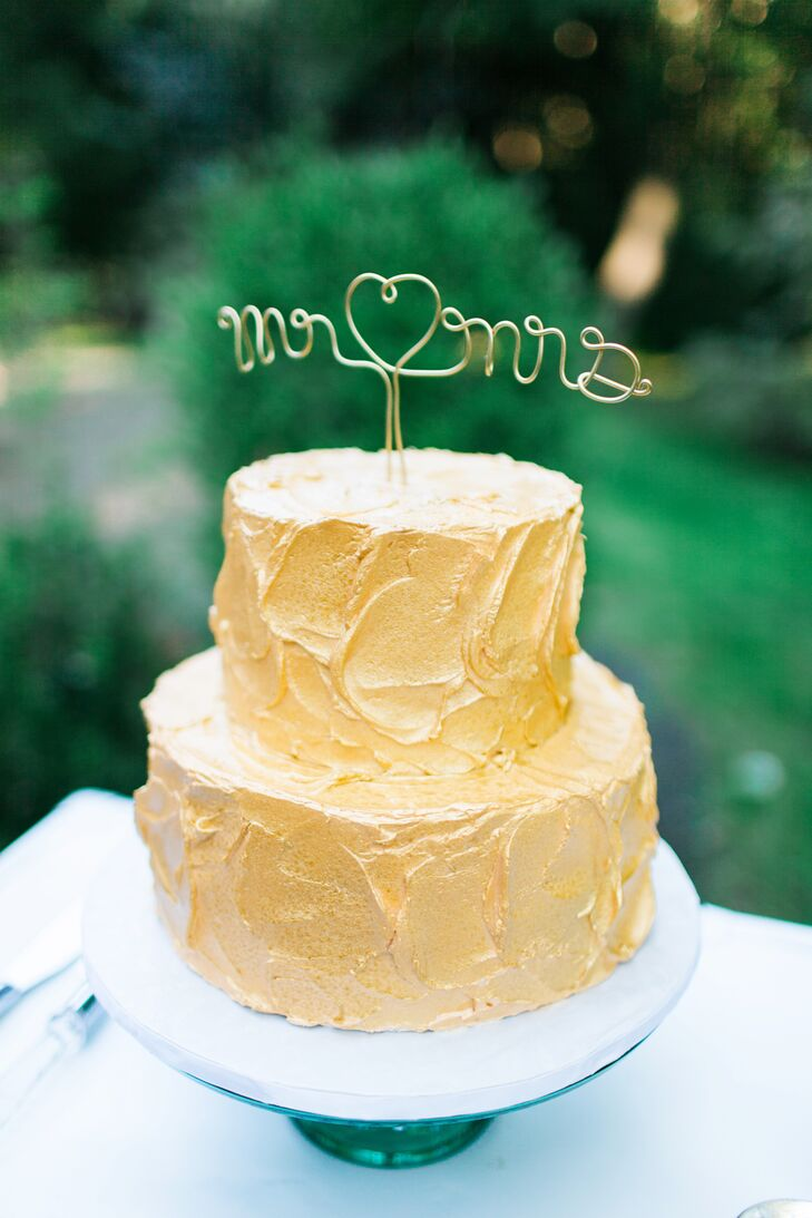 """A gold cursive """"Mr. & Mrs."""" cake topper stood on top of the two-tier gold-frosted cake."""